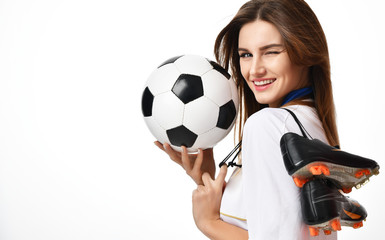 Fan sport woman player in red uniform hold soccer ball and boots celebrating winking on white