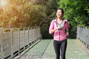 Young asian woman running on sidewalk in morning. Health conscious concept with copy space. Young sport asian woman running upstairs on city stairs. Fitness sport people and healthy lifestyle concept.
