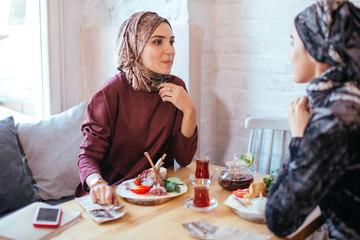 Two pretty Muslim women in cafe, friends meeting