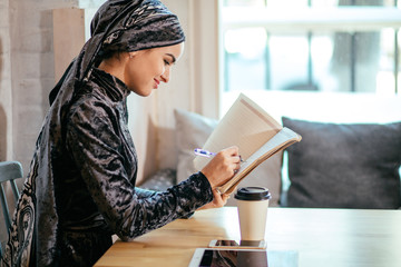muslim woman wearing red scarf writing beside notebook at cafe