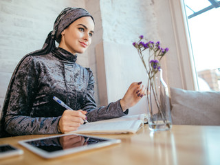 muslim woman working in cafe, writing on notepad
