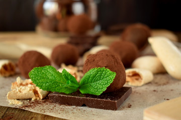 Chocolate truffles sprinkled with cocoa powder and leaves of mint