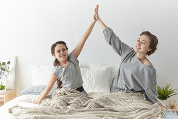 People, family bonds, happiness, joy and relaxation concept. Cheerful cute girl and her young mother giving each other high five wearing casual clothes, sitting on bed, celebrating great news