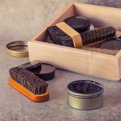 Care products for footwear. Wooden box with shoes brushes and round jars with cream on a gray background.  Toned photo.