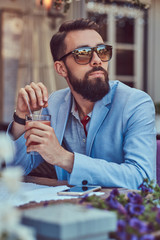 Portrait of a fashionable bearded male with a stylish haircut, holds a glass of a cappuccino, sitting in a cafe outdoors.