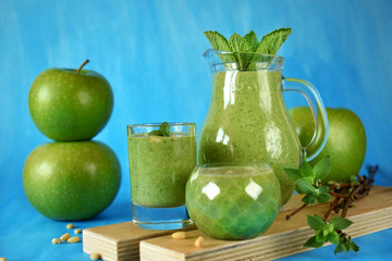 Green smoothie in glass vessels on blue background