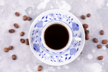 A beautiful porcelain coffee cup with hot black coffee. Coffee beans scattered around the background. Vintage china. A white-blue cup on a gray background.