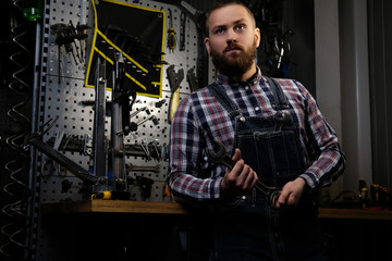 Portrait of a handsome stylish male with beard and haircut wearing a flannel shirt and jeans coverall, holds steel wrench, standing in a workshop.