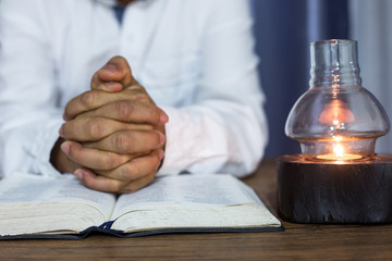 woman hands on bible. she is reading and praying over bible over wooden table bible.the man praying bible