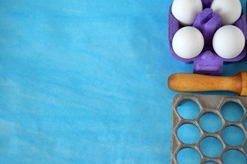 Eggs, flour and kitchen utensils for cooking homemade dumplings on blue background. Copy space