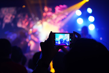 Audience keep taking photo and video at concert with their cellphone focus on the screen with blur background