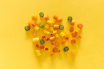 Assortment of colorful sweet handmade candy pieces arranged on yellow paper