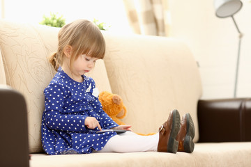 Cute little girl on couch use cellphone
