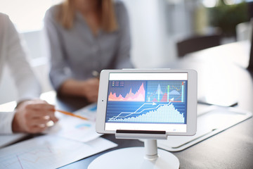 Tablet computer with stock data and blurred office meeting on background. Finance trading