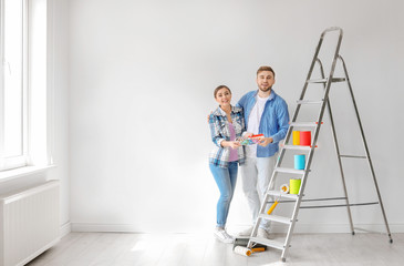 Young couple with color palette indoors