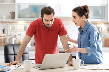 Young couple having argument about family budget in kitchen