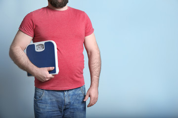 Overweight man with scale on color background