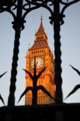 Close up of the clock face of Big Ben in Westminster on the Sunset. View through a forged fence. London, UK.
