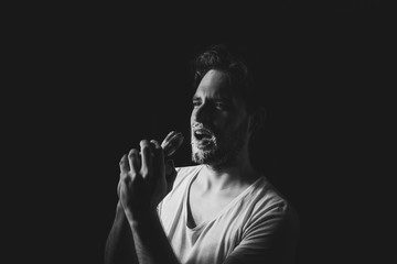Young handsome man sing to shaving brush on black background. Black and white studio portrait.