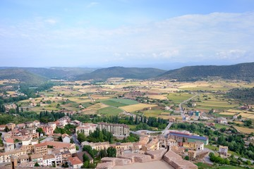 View from Cardona Castle. Sunlit large valley with colorful fields and small houses. The valley is surrounded by green mountains. Blue sky and white clouds. Summer. Catalonia, Spain.