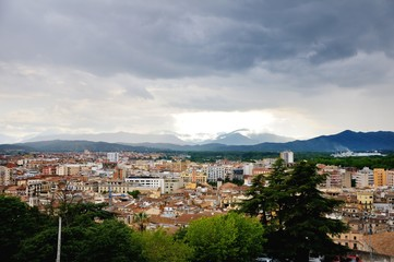 View of the city of Girona from the medieval pedestrian border wall. Roofs of houses, trees. Storm clouds over the city, somewhere sunlight makes its way through the clouds. Girona, Spain