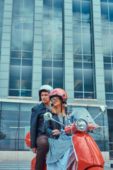 An attractive couple, a handsome man and sexy female riding together on a red retro scooter in a city.