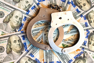 Dollars and handcuffs as an abstract symbol of financial crimes and corruption of officials and politicians