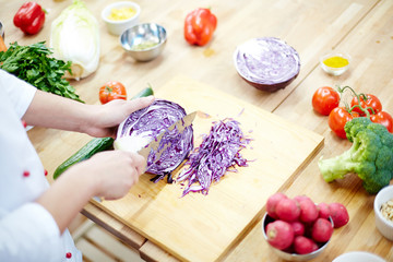 Hands of chef with knife cutting fresh cabbage on wooden board among other fresh vegetables in process of cooking
