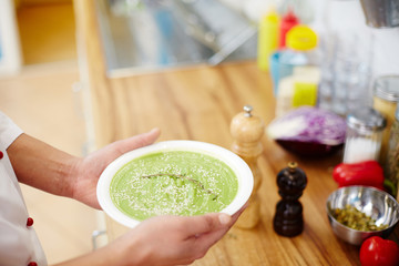 Hands of chef holding plate with broccoli cream soup seasoned with sesame seeds and thyme