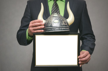 Best bull stock broker. Diploma template of best player for raising stock prices on the exchange. Businessman holding viking helmet and blank photo frame in hands.