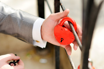 The hands of the groom keep the red lock in the form of a heart. Newlyweds hang the lock symbolizing everlasting love on the wedding day. Wedding tradition.