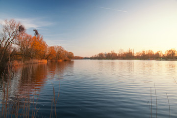 Panorama view of a lake with blue sky and golden sunset light. Südsee in Braunschweig, Germany