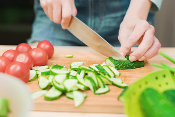 close-up of female hands cut into fresh cut cucumbers on a wooden cutting board next to pink tomatoes. The concept of homemade vegetarian cuisine and healthy eating and lifestyle