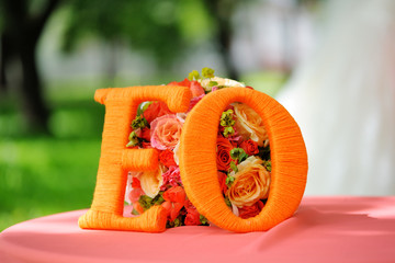 Bouquet of a bride on a table with a pink tablecloth with large orange letters E and O by the name of the bride and groom. Beautiful wedding bouquet.