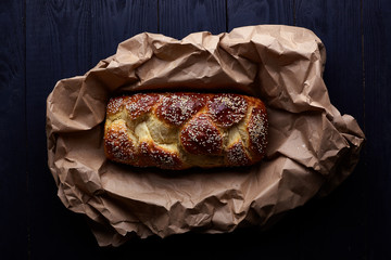Beautiful Arabic, oriental bread with sesame. A loaf of bread in dark tones lies on a sheet of craft paper. Appetizing addition to breakfast, lunch, dinner. Homemade loaf for toast and sandwiches.