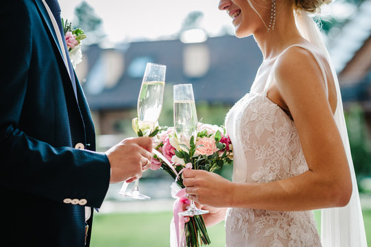 The bride and groom with a wedding bouquet, holding glasses of champagne standing on wedding ceremony under the arch decorated with flowers and greenery of the outdoor in the backyard banquet area.