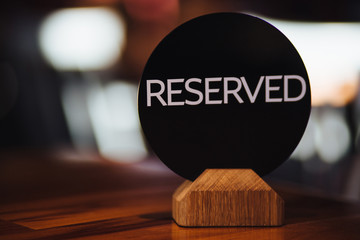 Reserved table in luxury restaurant or cafe. Reservation card on festive table shows occupied place by customers. Sign with inscription: Reserved written in capital letters