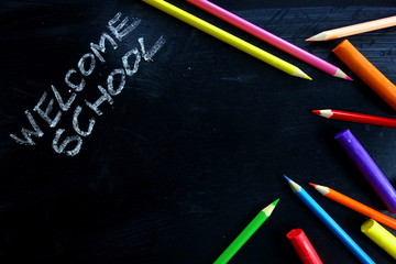 Welcome school text and colorful supplies on chalkboard, copy space for your design
