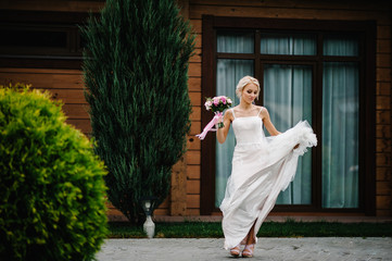 Portrait of an attractive bride with a wedding bouquet dancing and rotating, spinning on a wedding ceremony.