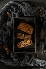 Pastries with raisin on a black wooden tray with dried fruit and cinnamon