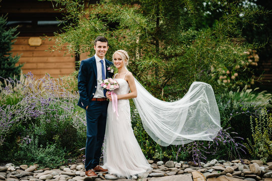Romantic couple newlyweds, bride and groom holding bouquet of pink, purple flowers and greens, greenery with ribbon in the garden, on wedding ceremony standing on stone. Outdoors.