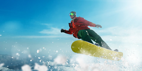 Snowboarder in glasses makes a jump, winter sport