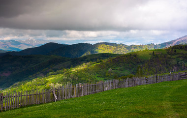 fence on the edge of the hillside. beautiful rural landscape of Carpathian mountains in springtime. forested hills under the heavy clouds in the distance