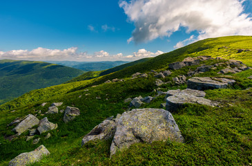 row of huge rocks on a grassy mountain. lovely summer scenery of Carpathian mountains. cloud approaching from behind the hill