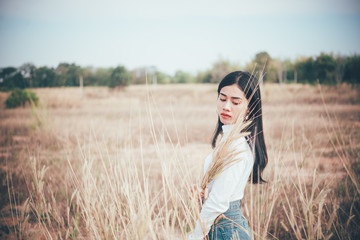 Happy asian woman with beautiful stand on fence at the field,lifestyle of single girl