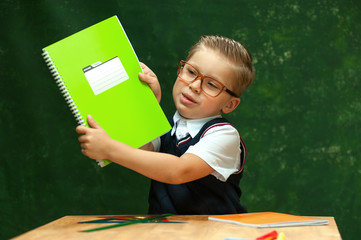Young elementary school student with blond hair wearing glasses shows large green notebook sitting behind wooden desk on dark green background