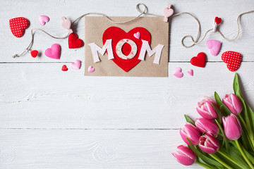 Background for congratulations for Mother's Day with greeting card, hearts and pink tulips