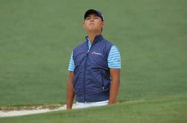 Kim Si-Woo of South Korea looks at his ball during final round play of the 2018 Masters golf tournament in Augusta