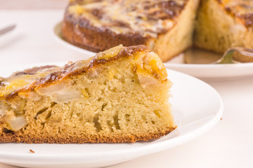 A piece of French apple cake on a plate on a light wooden background