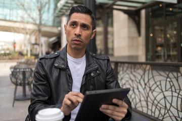 HIspanic man in city using tablet computer